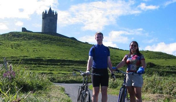 Enjoying a Romantic Cycle by Doonagore Castle in County Clare