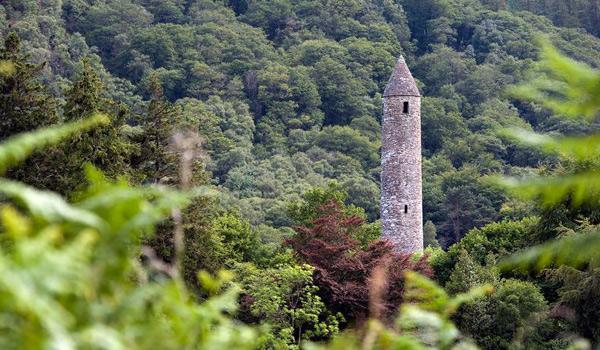The Distinctive Round Tower rises from among the trees at Glendalough, County Wicklow.