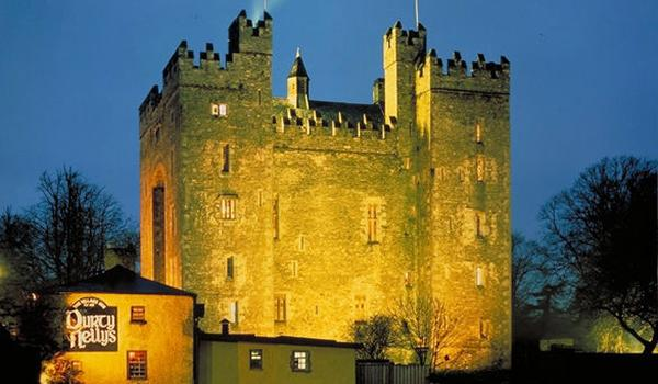 Bunratty Castle at dusk with World-Famous Durty Nelly's Pub in the foreground.