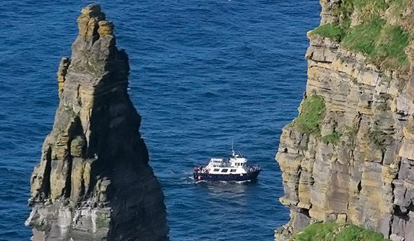 Cruise ship going by large rocks at cliffs of moher