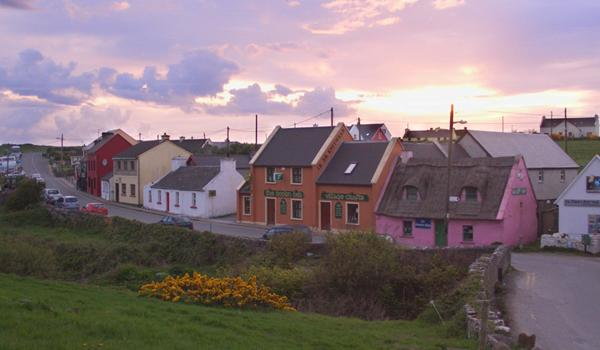 pint sunset with colorful village cottages in front in doolin county clare ireland