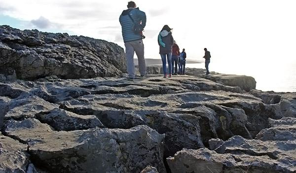 people walking along Ridged rocks along the Burren next to the ocean