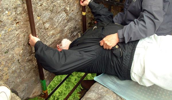 man bending backwards to kiss the blarney stone