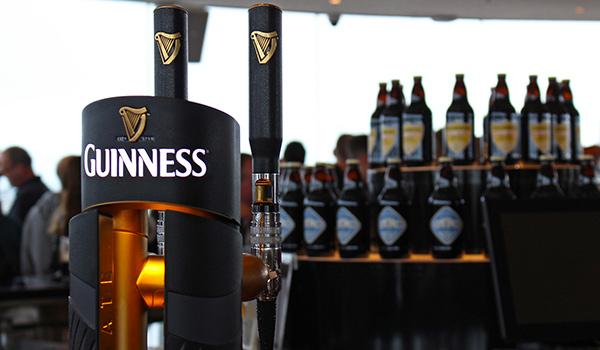 Guinness Storehouse Gravity Bar Pint Dispenser with Guinness Logo and bottles beers in background