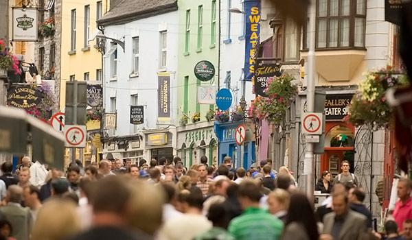 downtown galway street with hundreds of people walking and colorful architecture in back