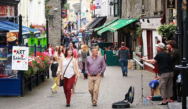 Man and woman walking up small street in kilkenny watching guitar street performer
