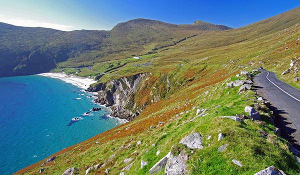 achill island beach and green rolling hills with winding road