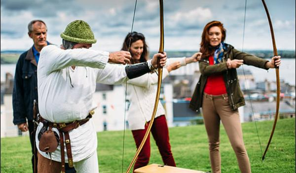 man training tourists to shoot bow and arrow medieval festival