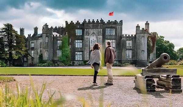 Couple looking at Birr Castle with surrounding green landscape