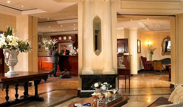 Inside Davenport Hotel Dublin lobby with people conversing at reception desk